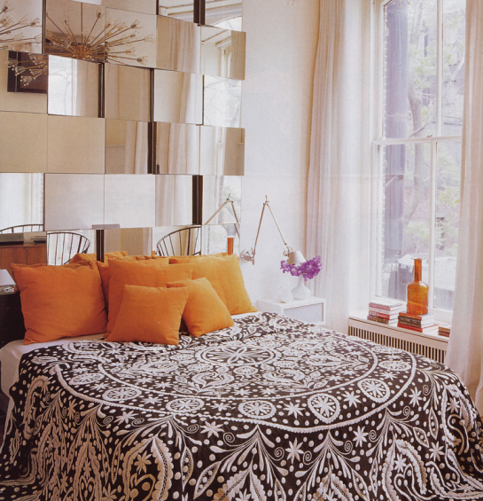 The brick ouse image bedroom with orange cushions